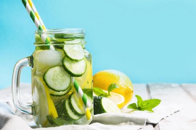 Agua dulce del verano con el limón, el pepino, el hielo y la menta en tarro de albañil en un fondo de madera.