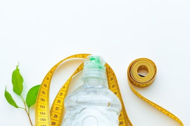 Agua embotellada para una vida sana y cinta métrica sobre un blanco