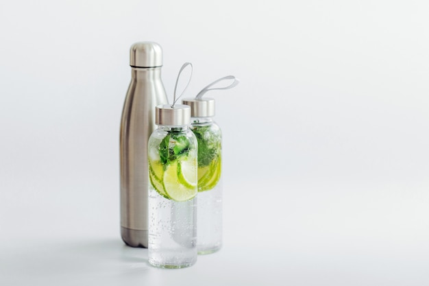 Agua fresca con infusión de limón y menta, cóctel, bebida desintoxicante, limonada en botellas reutilizables. bebidas de verano. concepto de salud.