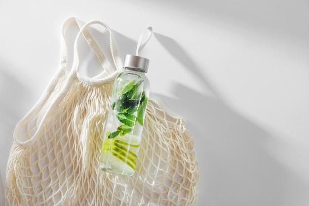 Agua fresca con infusión de limón y menta, cóctel, bebida detox, limonada en botellas reutilizables con bolsa ecológica. respetuoso del medio ambiente. estilo de vida sostenible.