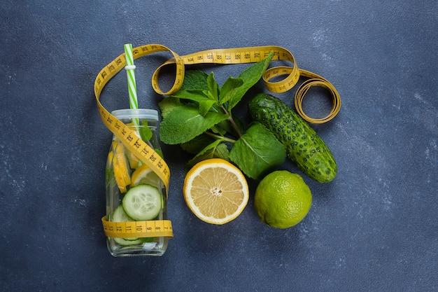 Agua fría detox con limón, pepino y menta en botella de vidrio. jugo natural, orgánico y saludable.