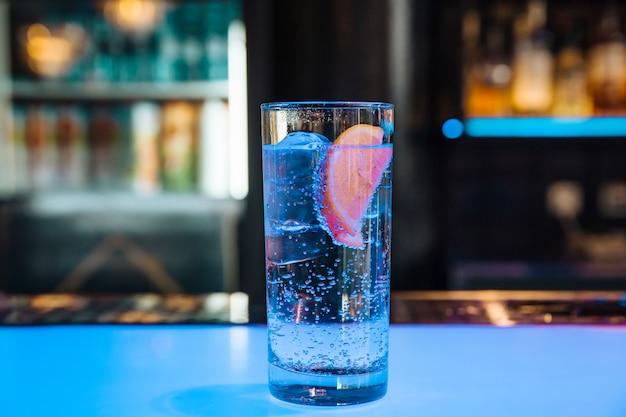 Agua fría en un sakan transparente con hielo con limón.