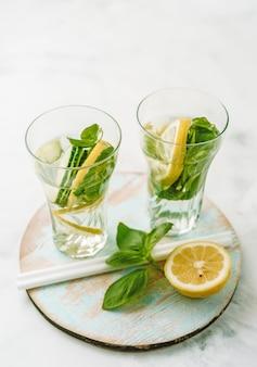 Agua infundida en dos vasos con limón, pepino y albahaca.