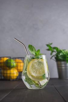 Agua infundida con limón, jengibre y menta en vaso. de cerca. bebida de desintoxicación saludable.