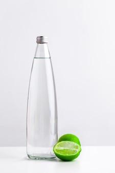 Agua de infusión de desintoxicación con cal en una botella de vidrio sobre un fondo blanco.