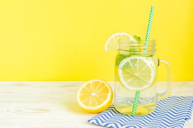 Agua de limonada cítrica con rodajas de limón y hojas de menta, bebida saludable y desintoxicante en verano