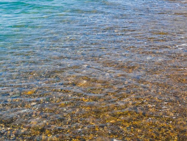 Bajo el agua de mar clara piedras visibles.