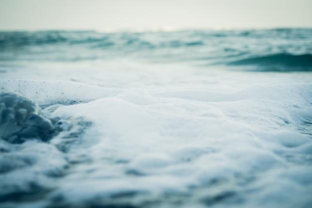 Agua de mar y espuma de primer plano, tono frío.
