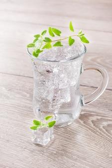 Agua mineral fría con cubitos de hielo y hojas de menta en un vaso transparente sobre una mesa de madera
