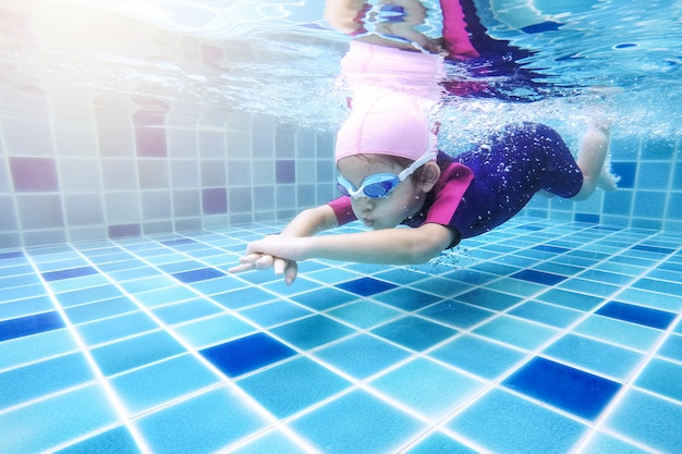 Bajo el agua niña linda está nadando en la piscina con su profesor de natación.