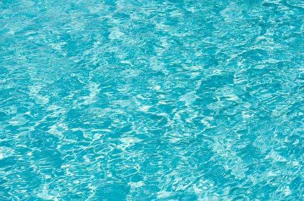 El agua de la piscina azul con reflejos del sol
