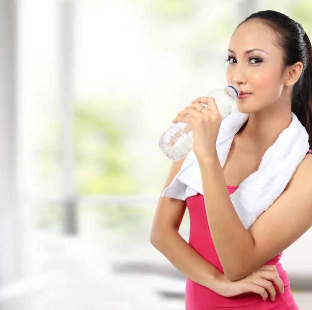 Agua potable asiática atractiva de la mujer sonriente