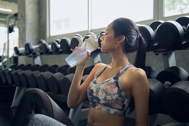 El agua potable de la chica joven asiática de la belleza en aptitud después de ella tenía algo se resolvía.