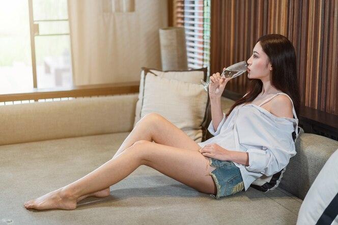 Agua potable de mujer en el sofá en la sala de estar