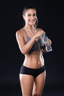 Agua potable hermosa de la mujer joven después de hacer ejercicio sobre fondo negro.
