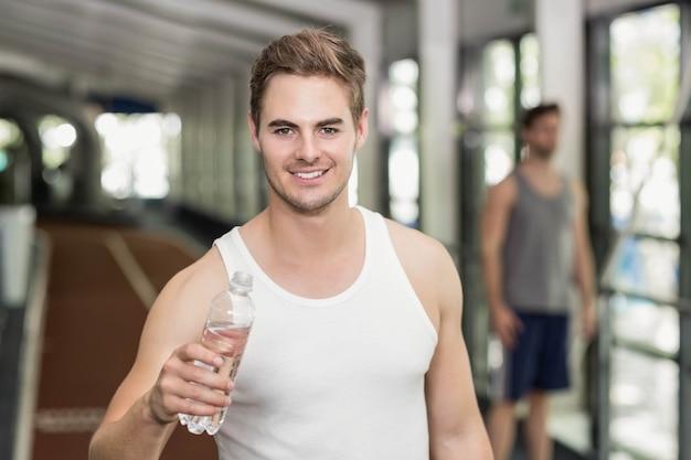 Agua potable del hombre apto en el gimnasio de crossfit