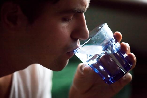 Agua potable del hombre deshidratado sediento joven que apaga la sed, opinión del primer