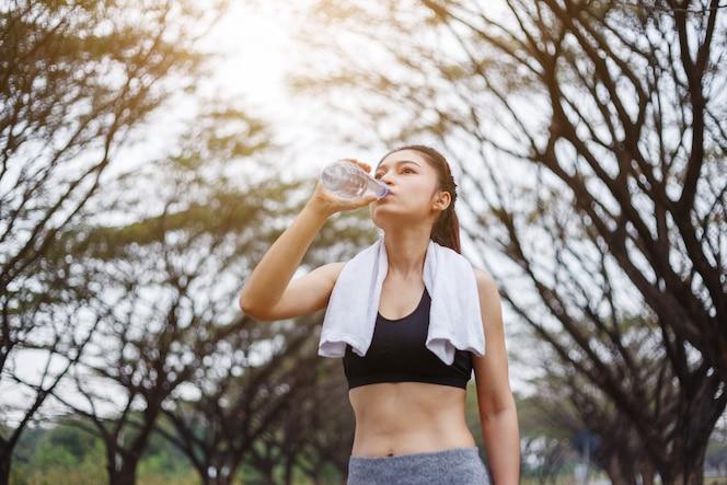 Agua potable joven mujer deportiva en el parque