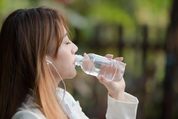 Agua potable de la mujer asiática de la botella por la mañana y música que escucha en fondo natural.