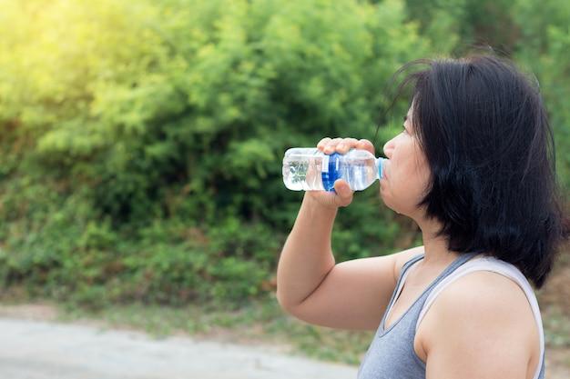 Agua potable de la mujer asiática después del ejercicio del deporte, mujer del deporte que sostiene la botella de agua pura