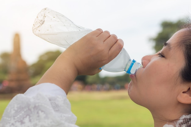 Agua potable de la mujer asiática joven hermosa después de la reclinación paseo en día de fiesta