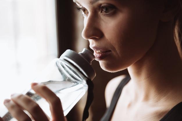 Agua potable de mujer bastante joven fitness.