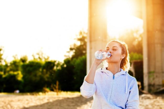 Agua potable de la mujer en luz del sol del verano