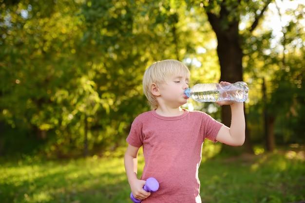 Agua potable del niño pequeño durante entrenamiento con pesas de gimnasia
