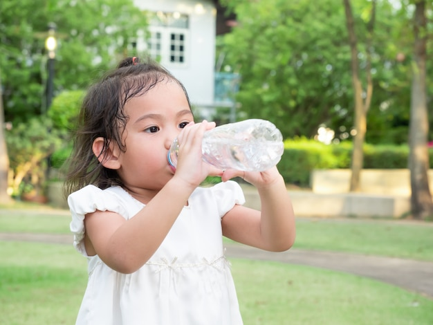 Agua potable de la pequeña muchacha linda asiática de la botella plástica después del juego que se ejecuta en el parque.