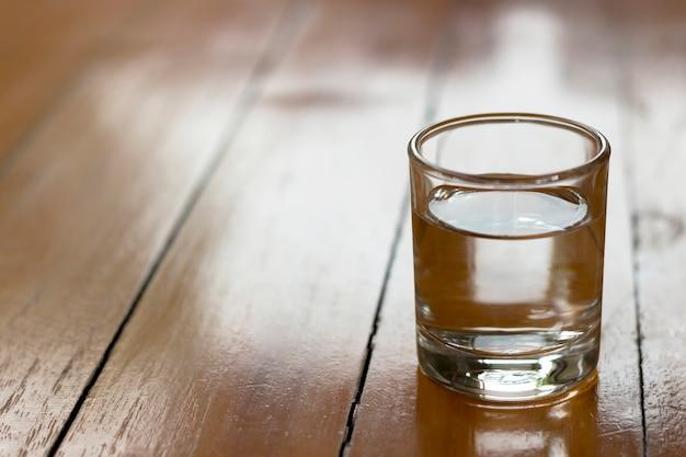 El agua potable en un vaso está en una mesa de madera.