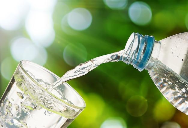 El agua potable se vierte de una botella en un vaso sobre fondo verde bokeh