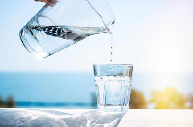 El agua purificada se vierte de una jarra de vidrio en un vaso.