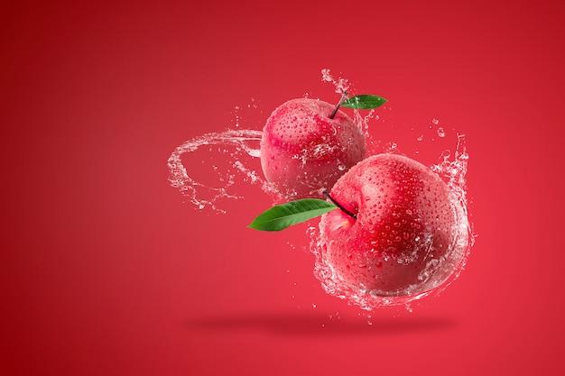 Agua que salpica en manzana roja fresca en fondo rojo.