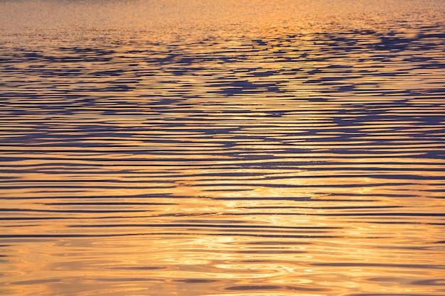 El agua del río con pequeñas olas durante la puesta de sol. textura de la superficie del agua
