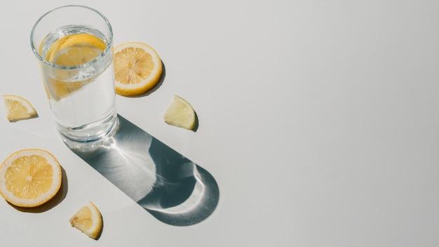 Agua con rodajas de limón y copia espacio de fondo