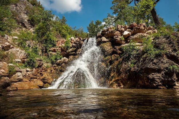 El agua se rompe a través de las piedras, una vista de la cascada. naturaleza colorida, un camino, descanso.