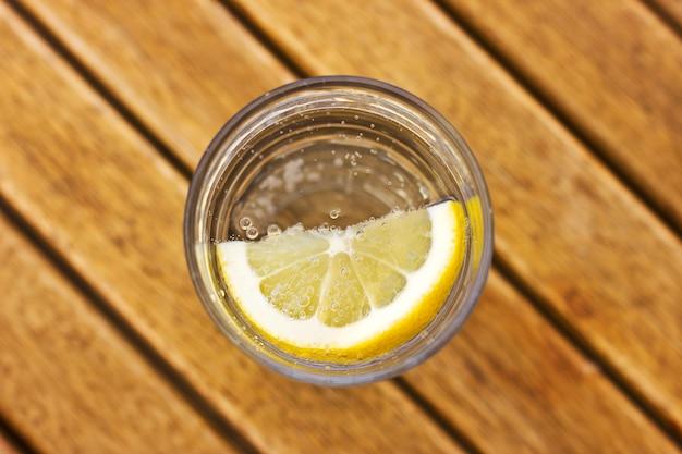 Agua de soda carbonatada con limón en un vaso con burbujas en una mesa de madera marrón