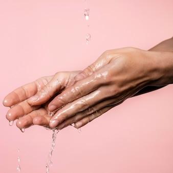 Agua vertida en manos de mujer