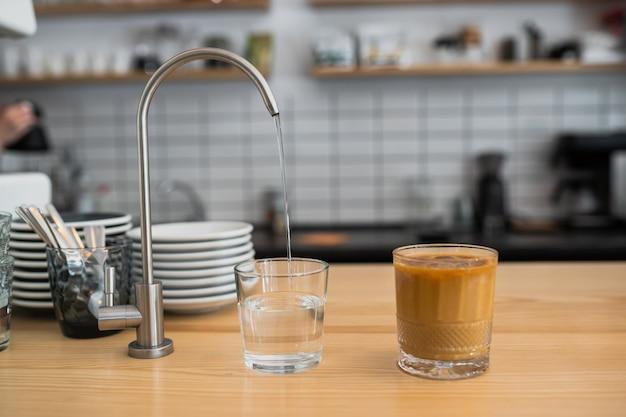 El agua se vierte de un grifo en un vaso