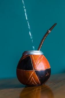 El agua se vierte en la taza mate tradicional