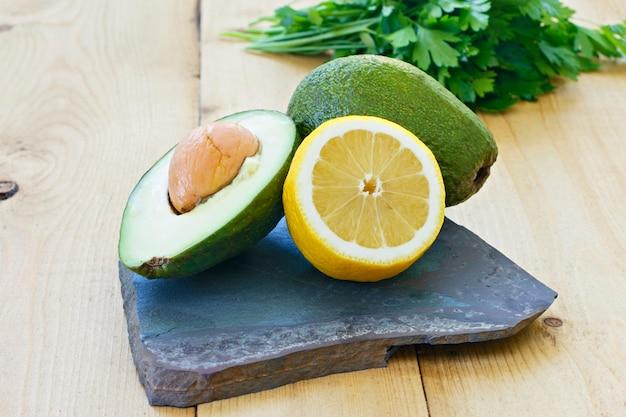 Aguacate entero y limón, perejil o cilantro sobre una tabla de piedra