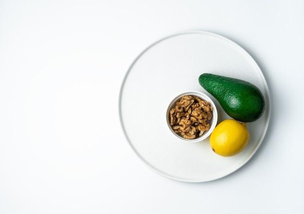 Aguacate maduro y limón y nueces sobre un fondo blanco. vista superior con espacio para copiar. el concepto de alimentación saludable.
