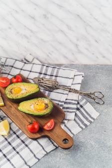 Aguacate a la mitad con huevo york; rodajas de tomate y limón en una tabla de cortar sobre la servilleta con pinzas
