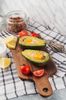 Aguacate a la mitad con huevo york; los tomates rodaja de limón en la tabla de cortar sobre la servilleta