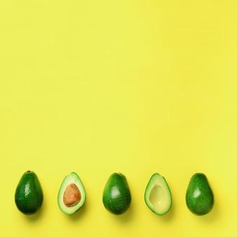 Aguacate orgánico con semilla, mitades de aguacate y frutas enteras sobre fondo amarillo.