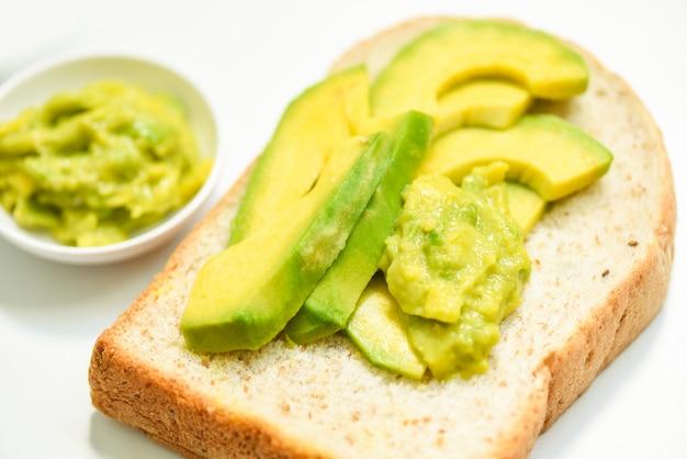 Aguacate en rodajas y tostadas de aguacate sobre fondo blanco placa frutas concepto de comida saludable