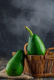 Aguacates con saco en una cesta en madera y pared de yeso, vista lateral.