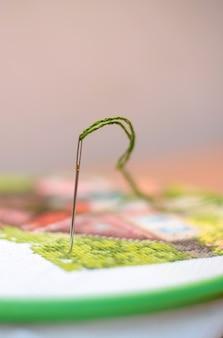 Una aguja con hilo verde.