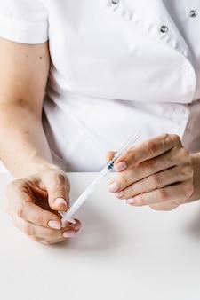 Aguja en manos de médico o cosmetóloga en guantes azules.