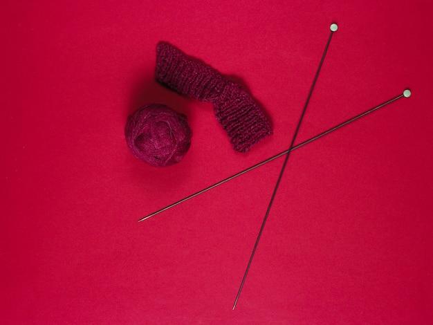 Agujas de tejer, bolas de hilo, hilo en la mesa roja.